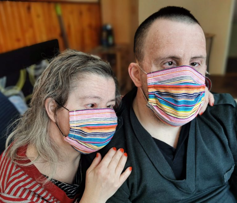 A couple with down syndrome wearing masks for COVID.