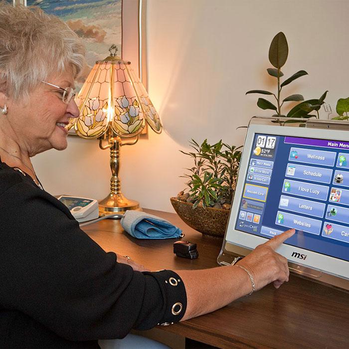 Safety Net Program senior using GrandCare touchscreen